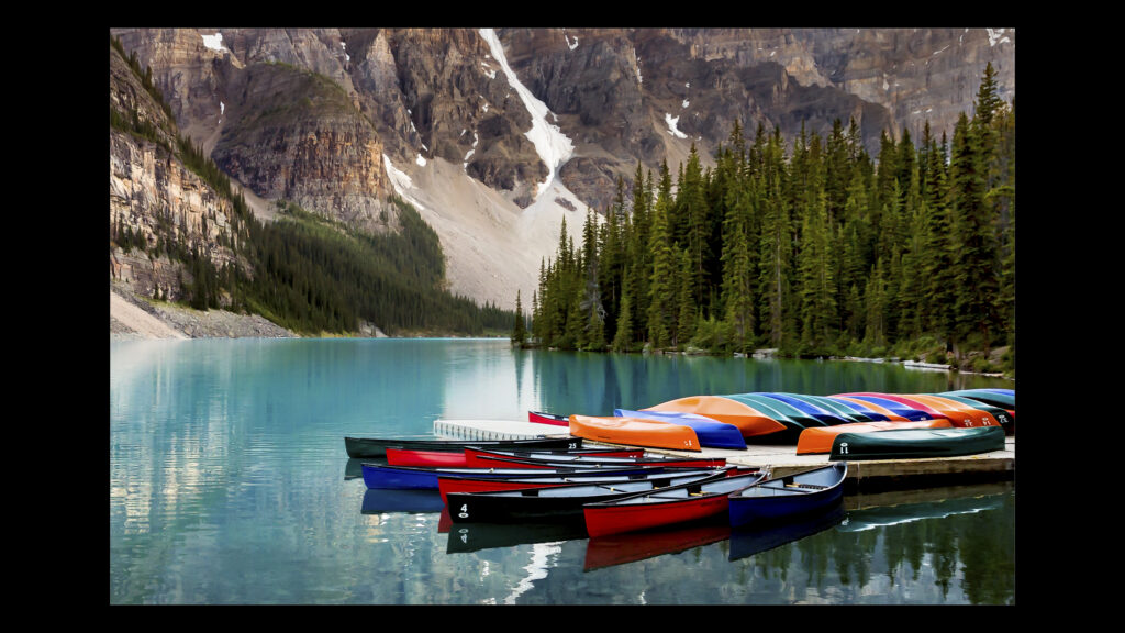 Image of canoes at Moraine Lake with blue water and mountains in the background.