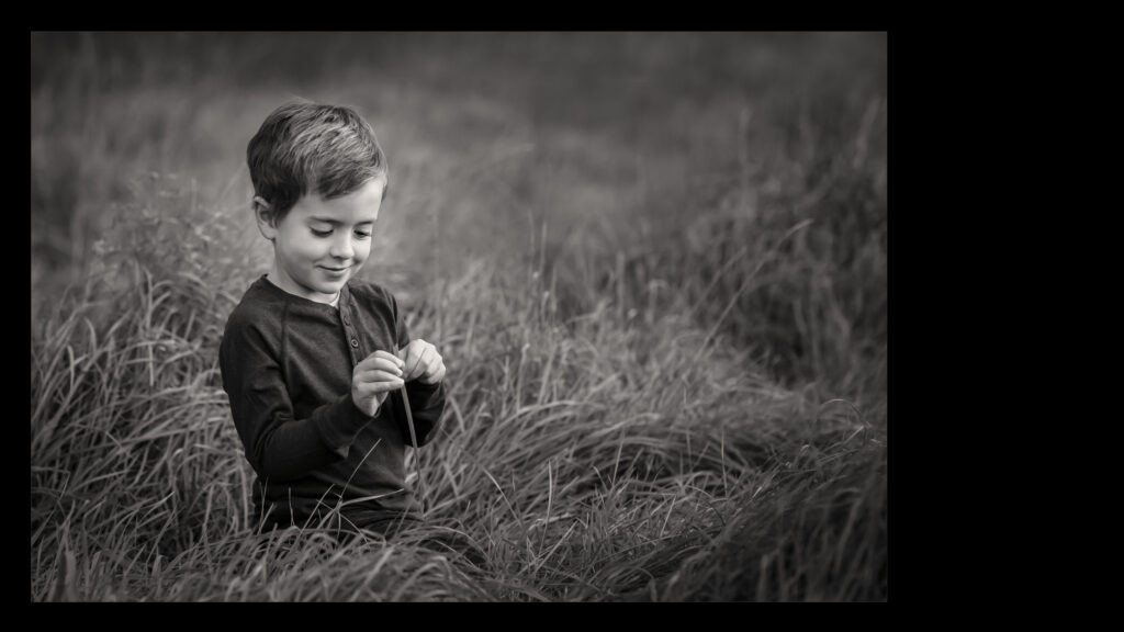 Black and White Image of Boy in Field playing with long grass.